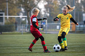 Two young female soccer teams competing for the ball during a football match on a sunny autumn afternoon