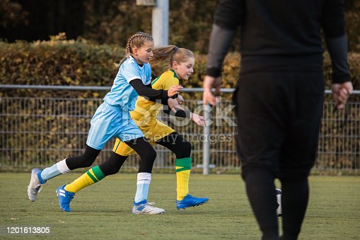 Two young female soccer teams competing for the ball during a football match on a dark autumn evening