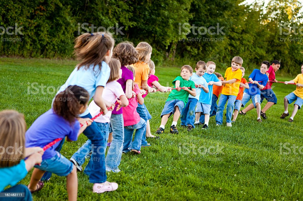 Girls playing tug-of-war against boys outside royalty-free stock photo