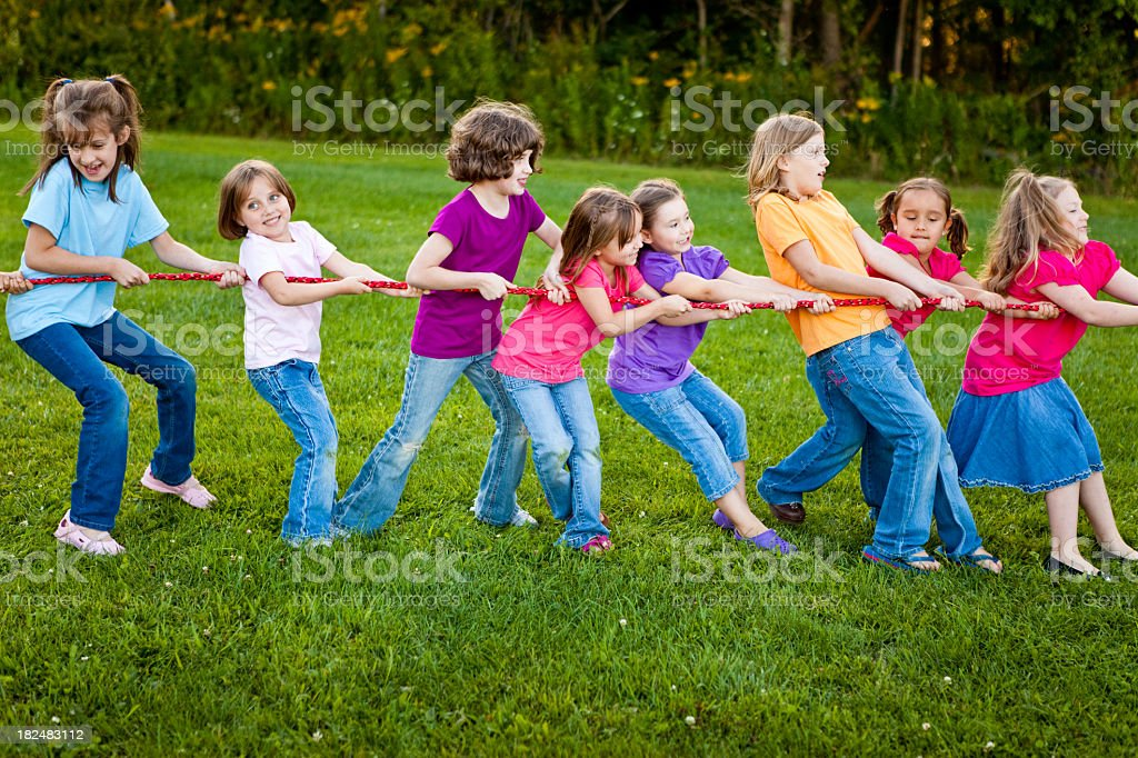 Girls Playing Tug-of-War Game Outside royalty-free stock photo