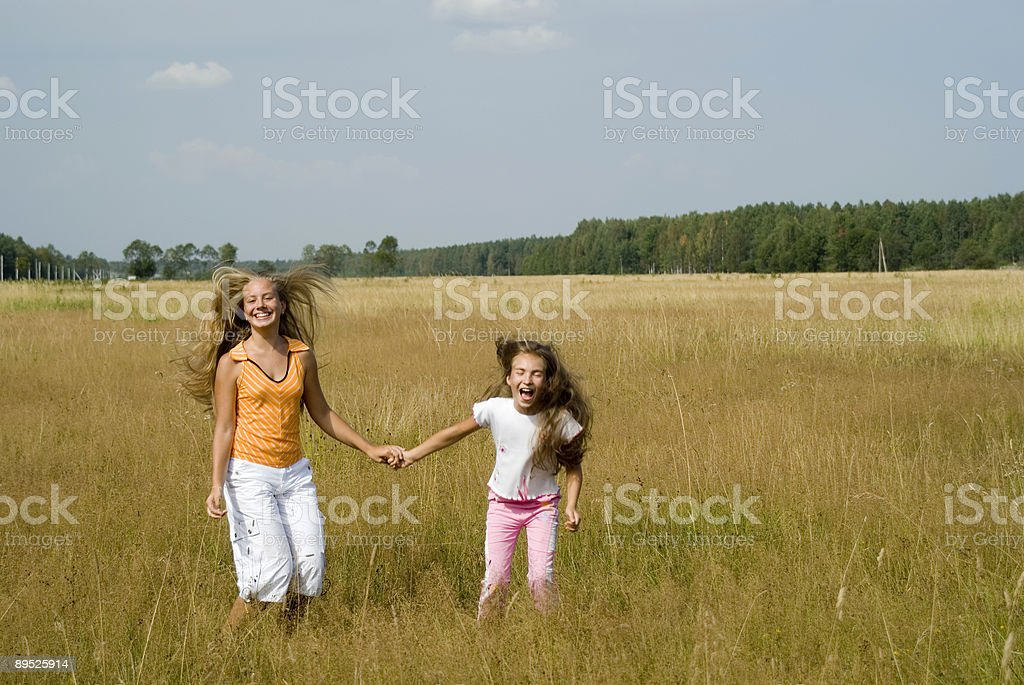 Girls plays on a meadow II royalty-free stock photo
