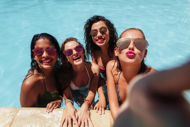 mädchen posiert für gruppe selfie im pool - happy weekend bilder stock-fotos und bilder