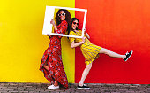 istock Girls posing with empty picture frame 1135152747