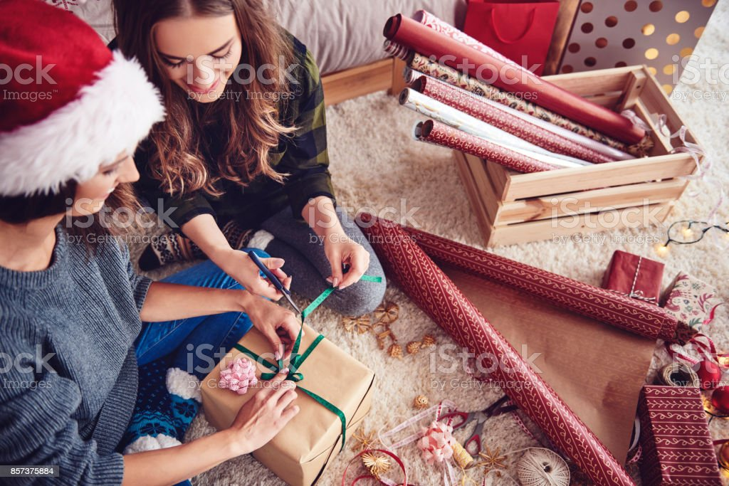 Girls  preparing a present for christmas Girls  preparing a present for christmas Adult Stock Photo