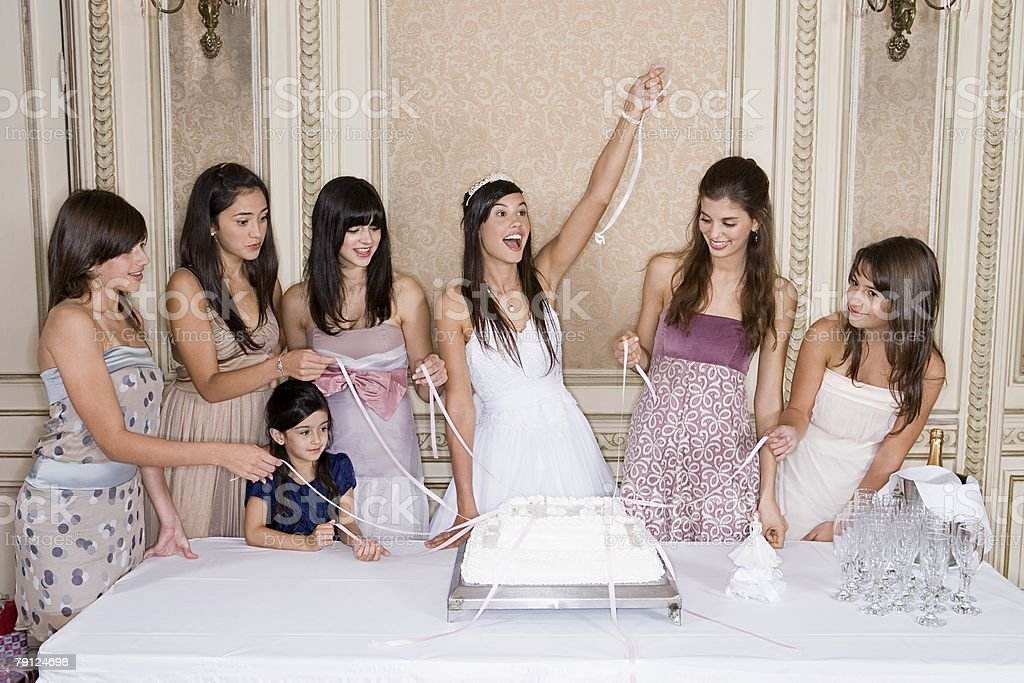 Girls pulling ribbons from cake stock photo