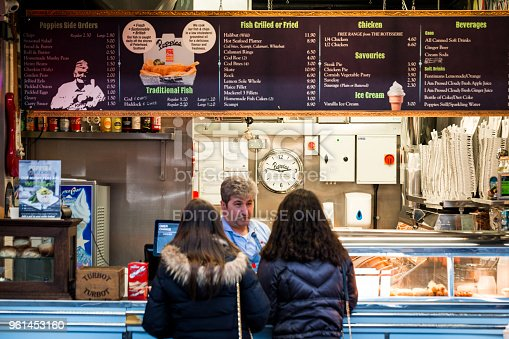 London, UK - 25 January, 2018: color image depicting two girls placing their food order at a fish and chips restaurant at Spitalfields Market in east London, UK. A mid adult caucasian man is taking their order, while behind him are extensive menus detailing the food on offer at this particular fish and chip shop. Room for copy space.