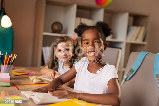 Two beautiful little girls sitting at a desk, reading books and studying for school
