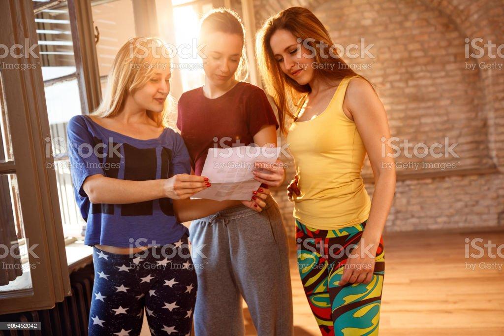 Girls reading paper together indoor zbiór zdjęć royalty-free