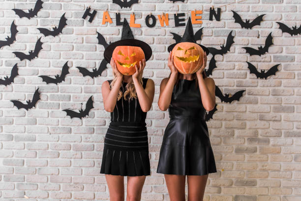 Girls ready for Halloween party Beautiful girls in black dresses and witch hats are holding scary pumpkins, on background decorated for Halloween costume stock pictures, royalty-free photos & images