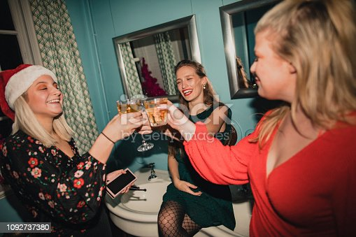 Three young women are toasting their glasses in the bathroom of a house party.