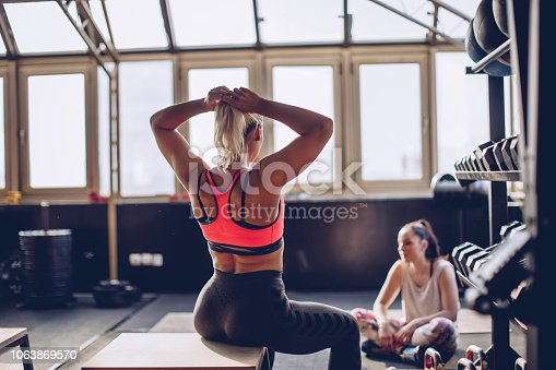 Two women, fit girls taking a break after training in gym, rear view.