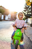 Small girl is having fun outdoors riding her motorcycle.