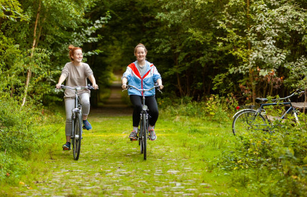 Girls riding a bike outdoors in the forest stock photo