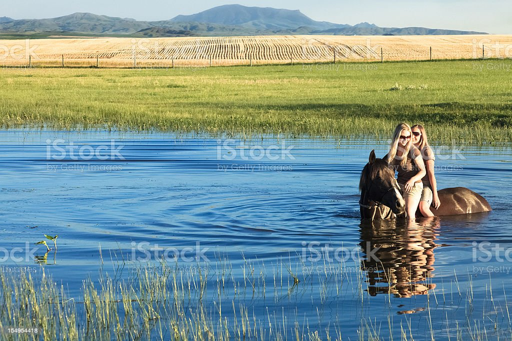 Girls Riding Horse In A Pond stock photo
