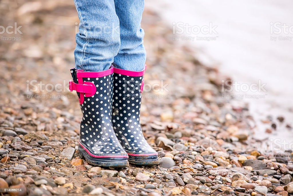 Girl's Rubber Boots Standing Next to River stock photo