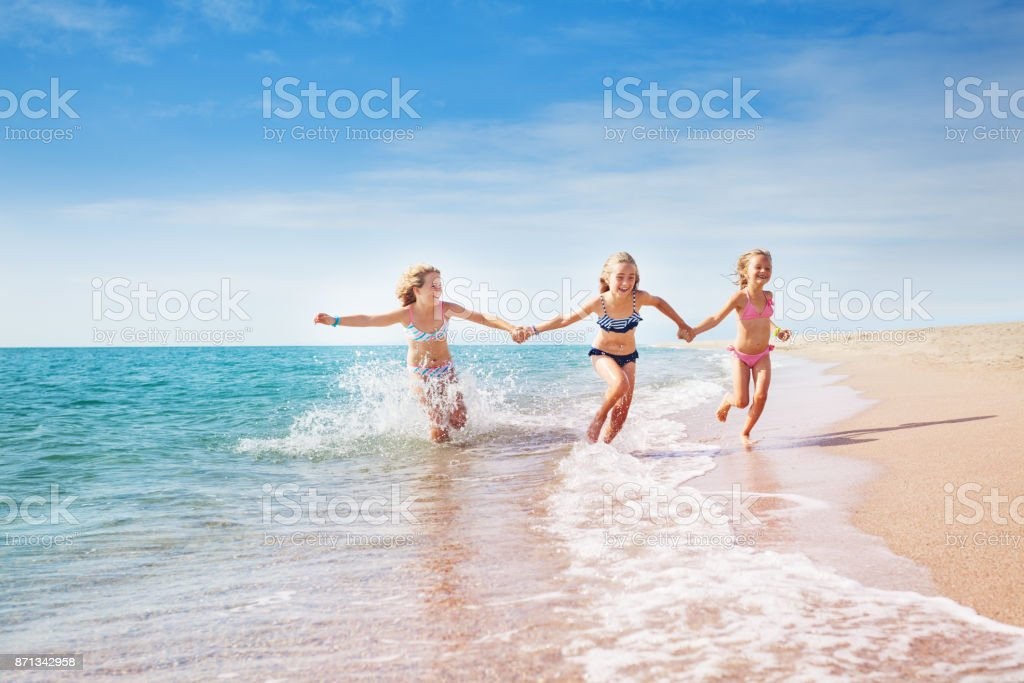 Girls running in sand and waves of sunny beach stock photo