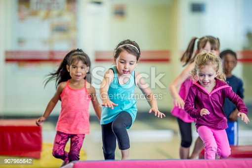 A group of preschool kids are indoors in their school gym. They are wearing casual clothes. Three girls are running and leaping onto a gymnastics mat.