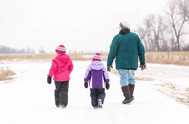 mädchen & senior oma zu fuß im schnee - kinder winterstiefel stock-fotos und bilder