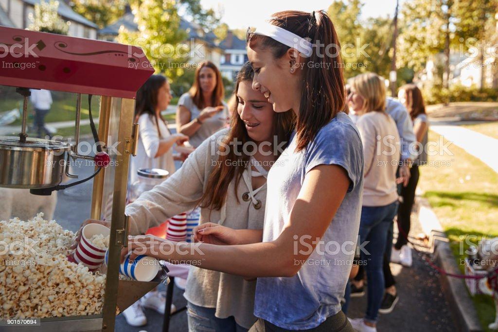 Girls serve themselves popcorn at neighbourhood block party stock photo
