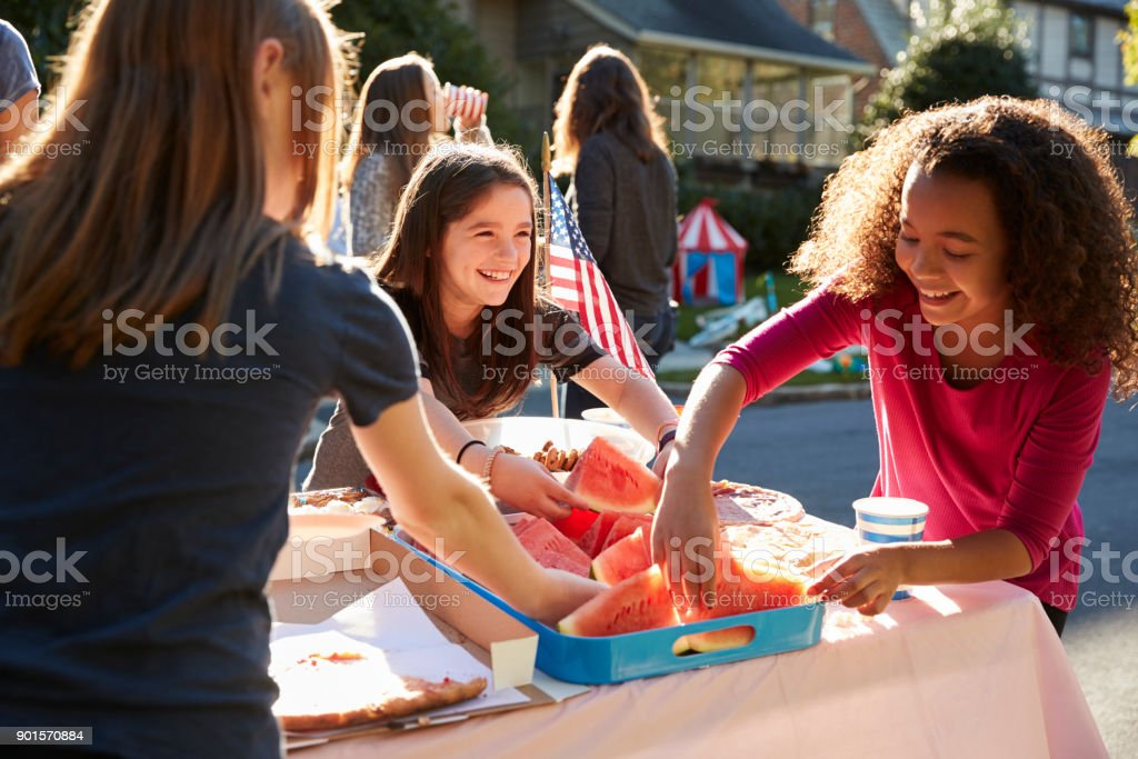 Girls serving themselves watermelon at a block party stock photo