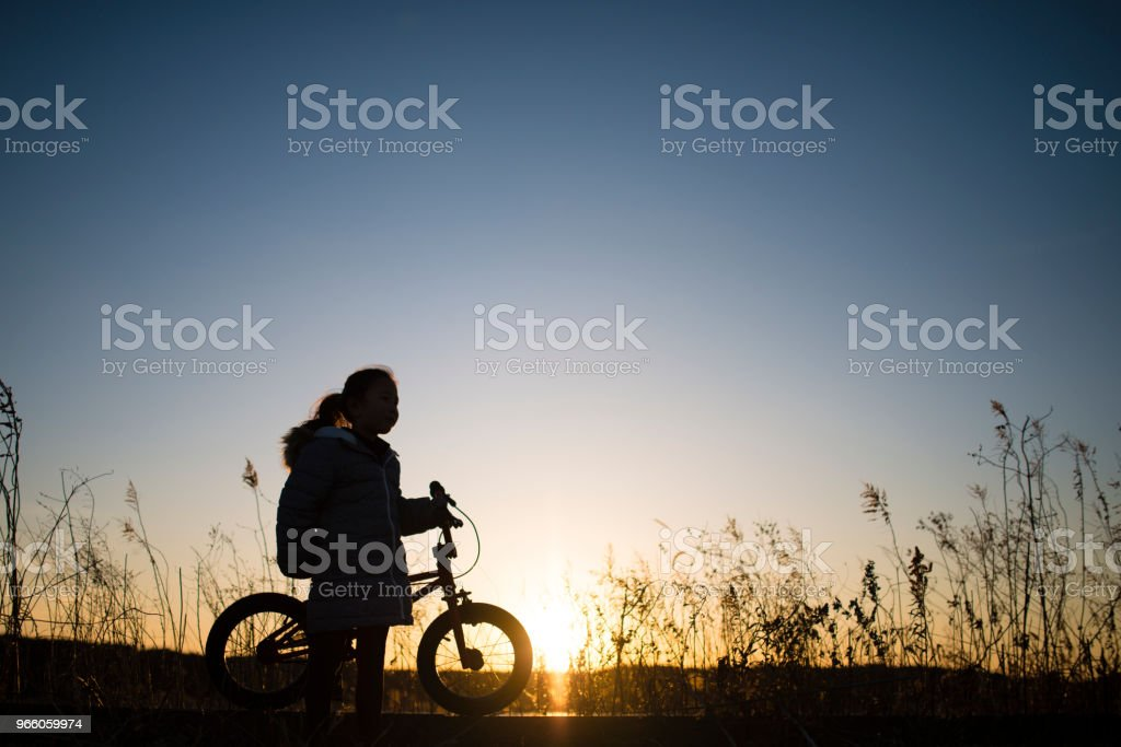 Flickor siluett cyklar - Royaltyfri Aktiv livsstil Bildbanksbilder