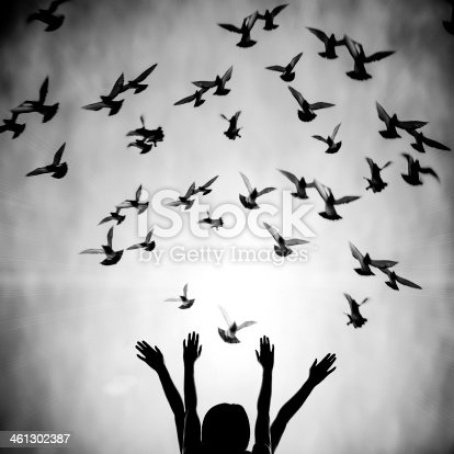 istock Girl's silhouette with doves flying above her 461302387