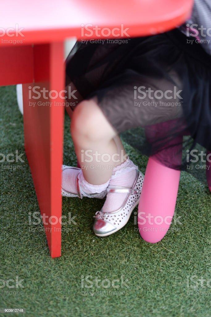 Mädchen sitzen auf Kunststoff-Stuhl unter Schreibtisch. – Foto
