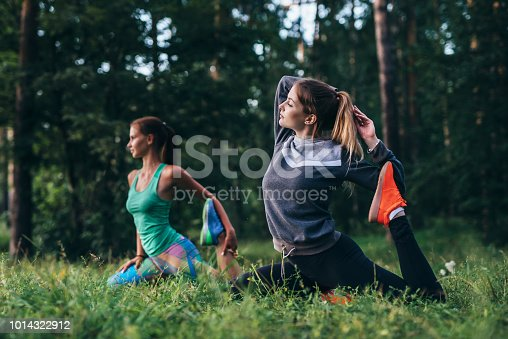 Girls sitting in one leg king pigeon pose during training session in yoga camp.