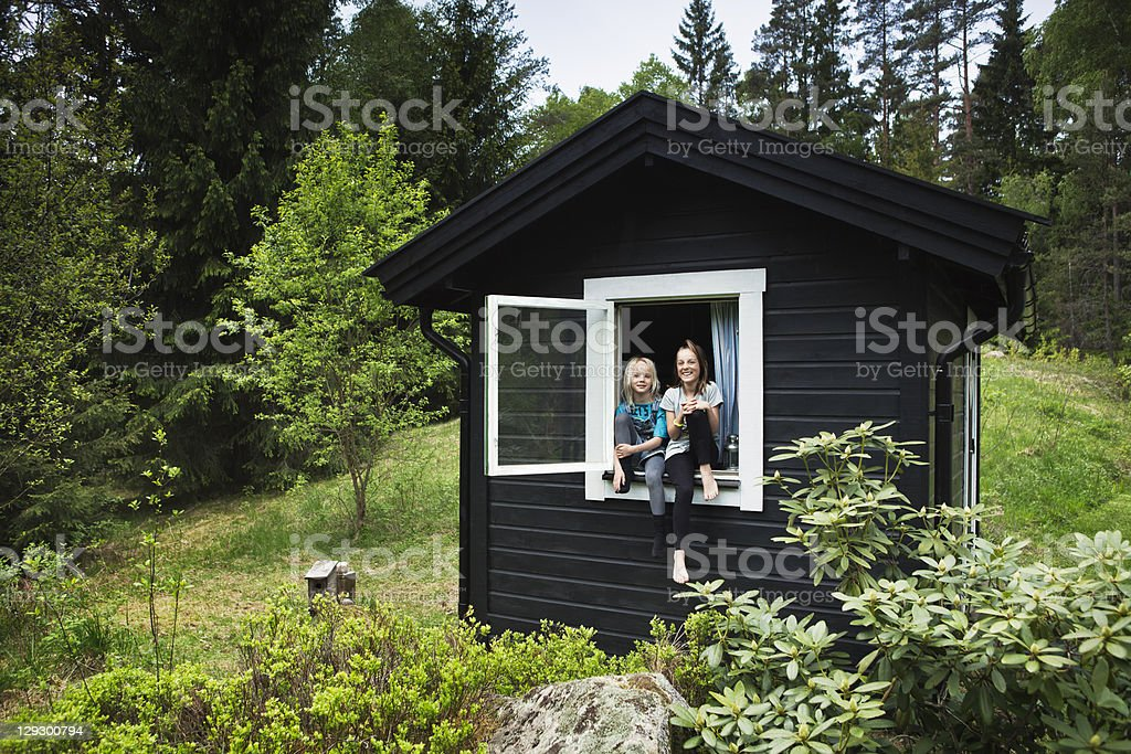 Girls sitting in window of shack stock photo
