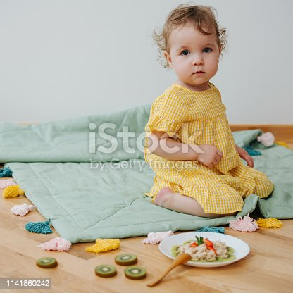 istock Girls sitting next to a plate of oatmeal decorated with fruits 1141860242