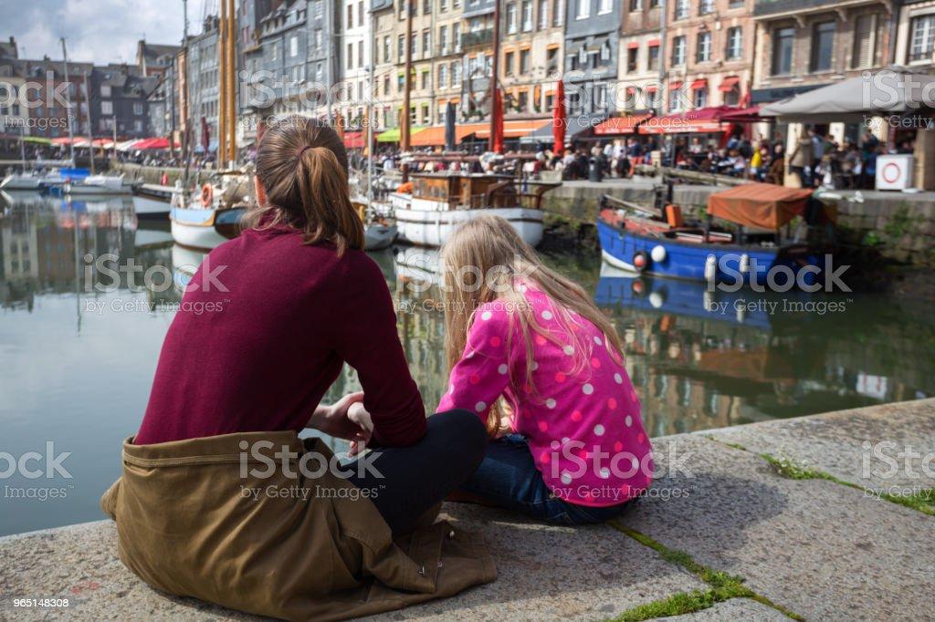girls sitting on background famous French city Honfleur zbiór zdjęć royalty-free