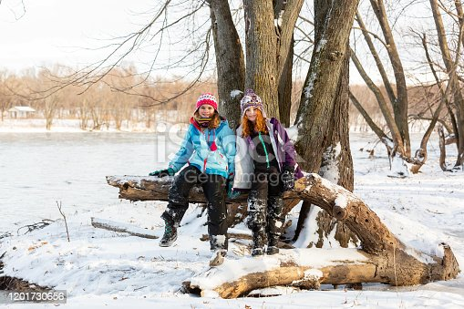 Two young girls (sisters) sitting on a fallen tree log on the bank of the Mississippi River. Taken on a winter day with snow on the ground.