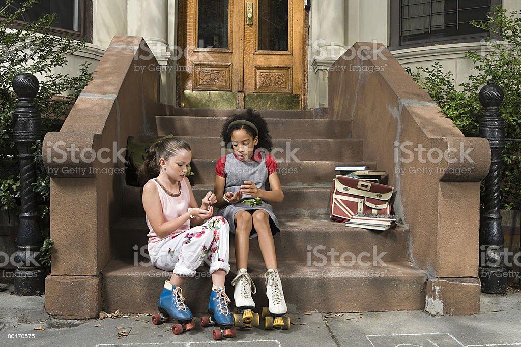 Girls sitting on steps stock photo