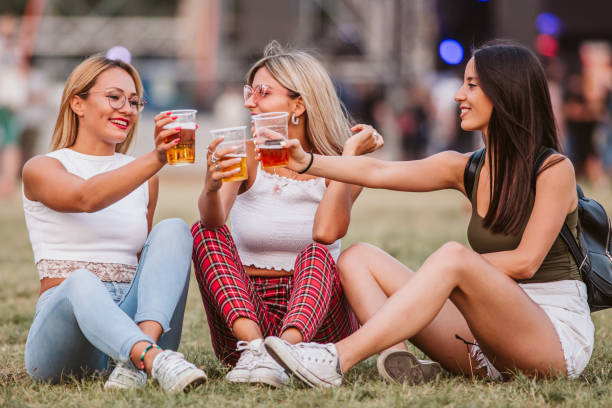 Girls sitting on the ground and cheering with beer at music festival stock photo