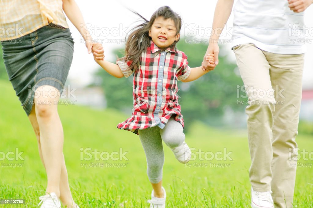 Girls skipping hand in hand with parents royalty-free stock photo
