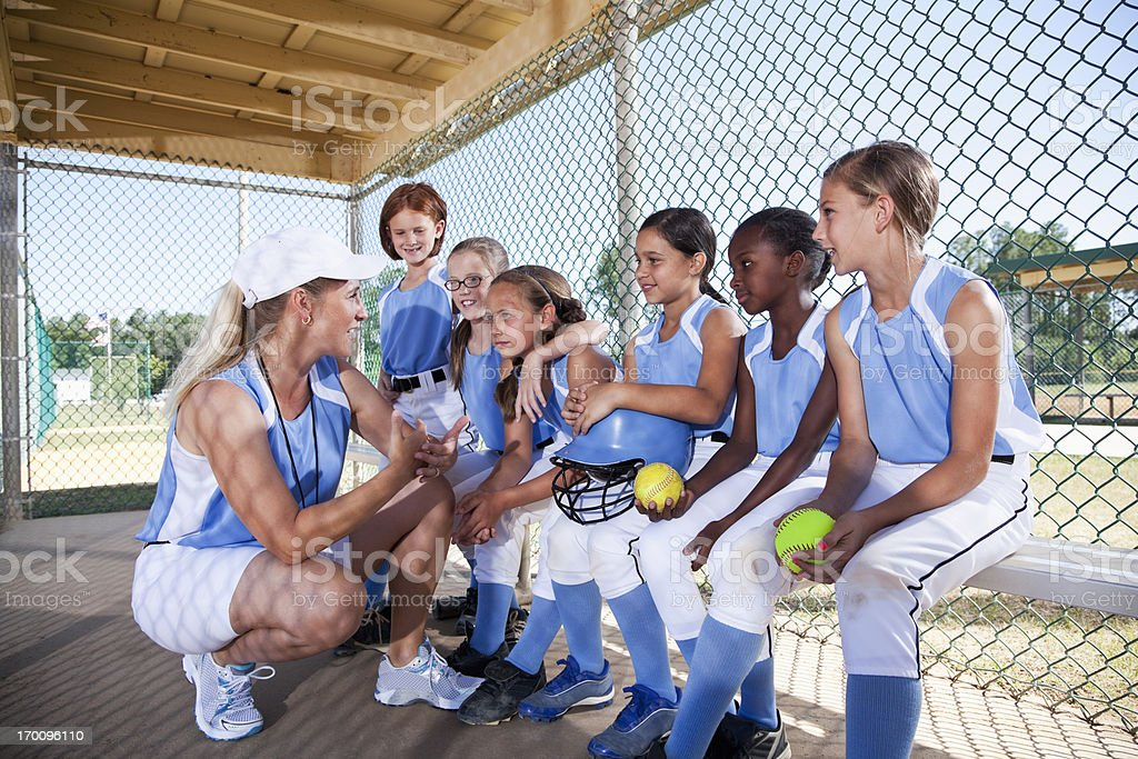 Girls softball team in dugout with coach stock photo