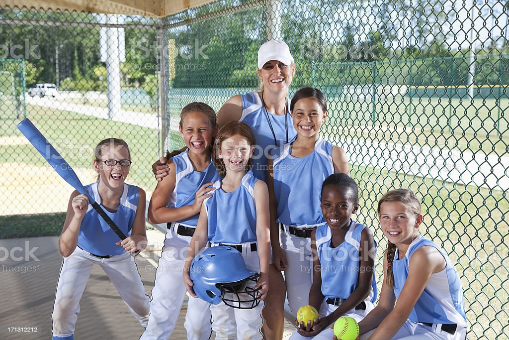 Girls softball team in dugout with coach royalty-free stock photo