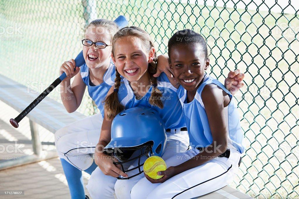 Girls softball team sitting in dugout stock photo