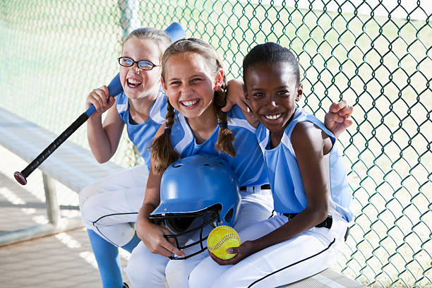 Girls softball team sitting in dugout Multi-ethnic girls (9 years) on softball team at the ball park, sitting in dugout. baseball sport stock pictures, royalty-free photos & images