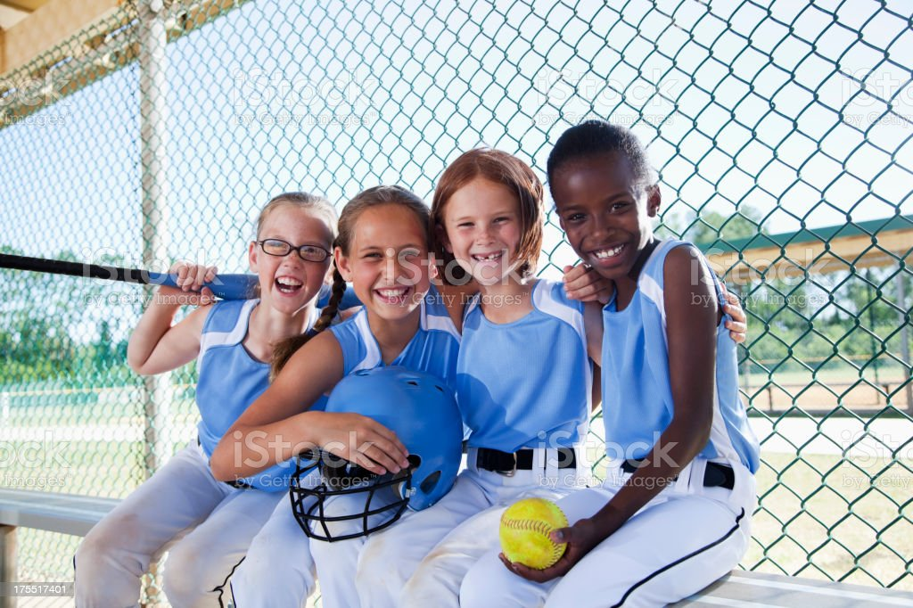 Multi-ethnic girls on softball team at the ball park, sitting in...