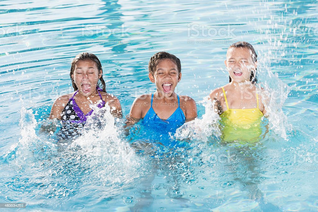 Girls splashing in swimming pool. stock photo