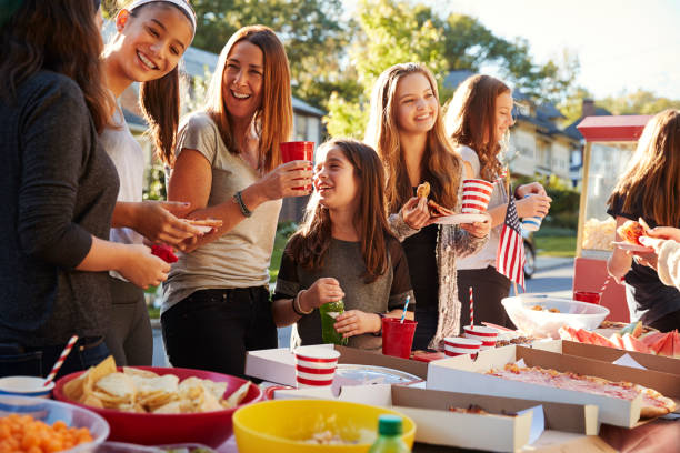 Girls stand talking at a block party food table, close up stock photo