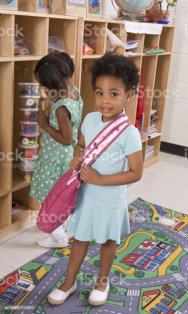 Girls (4-5) standing by cubbyhole royalty-free stock photo