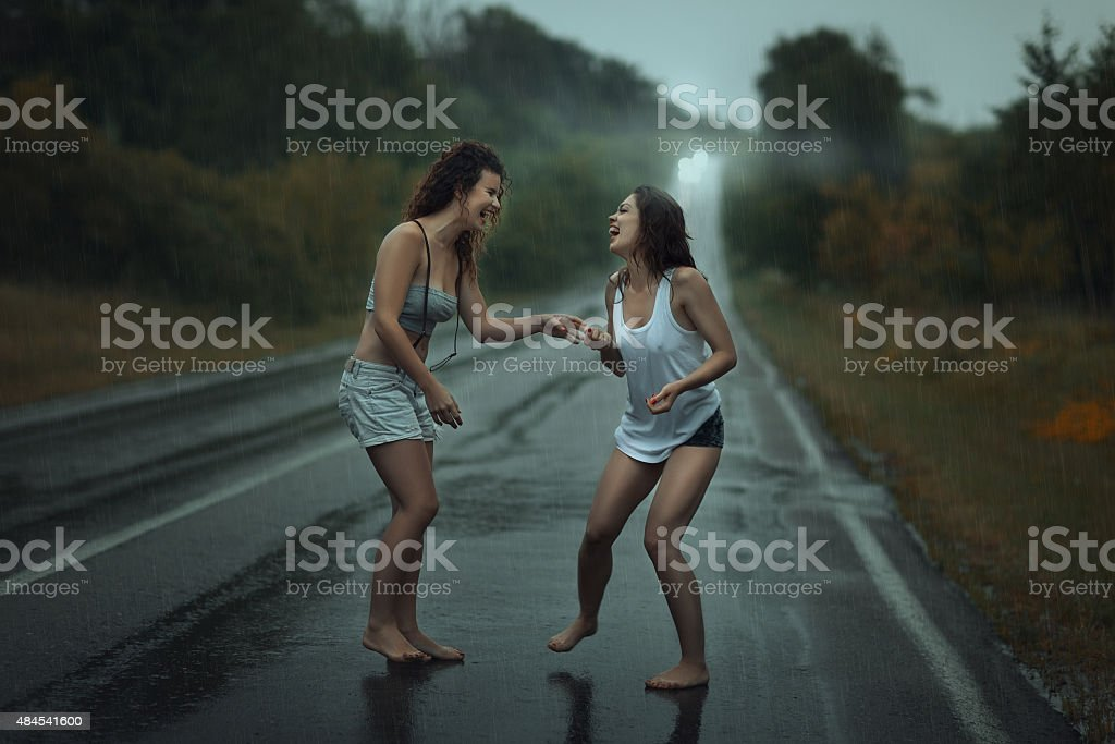 Girls standing in the rain on roadway. stock photo