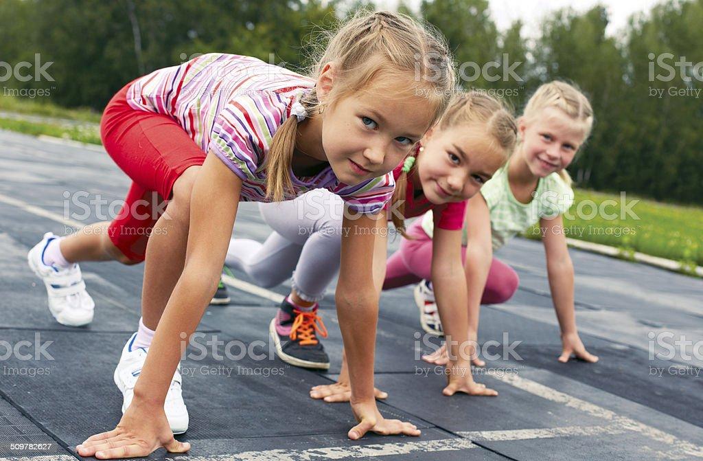 girls starting to run on track stock photo