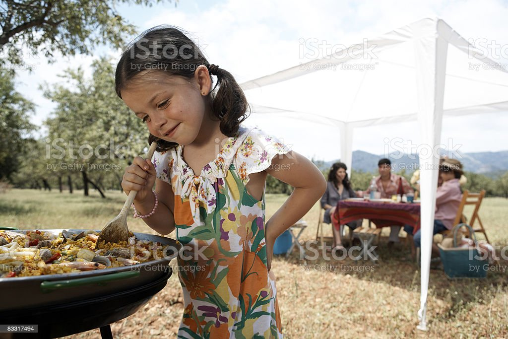 girls stiring paella outdoors royaltyfri bildbanksbilder