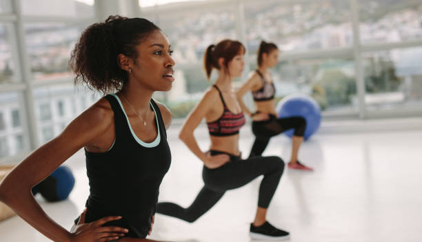 Girls stretching in gym class Group of young women exercising at the gym. Three females  in a stretching class at health club. exercise class stock pictures, royalty-free photos & images
