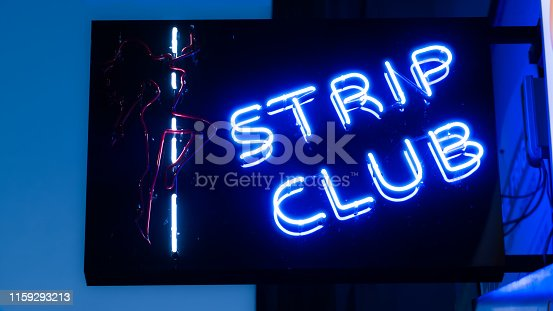 Girls strip club blue neon sign and woman silhouette.