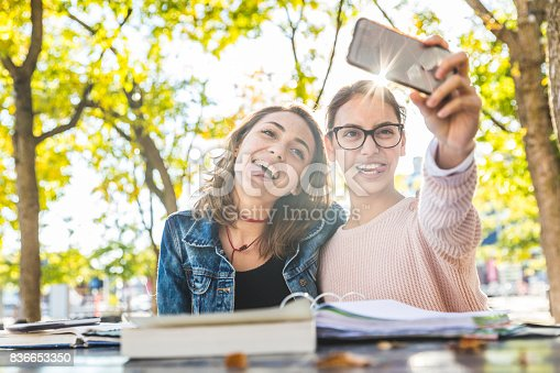 istock Girls studying and taking a funny selfie at park 836653350