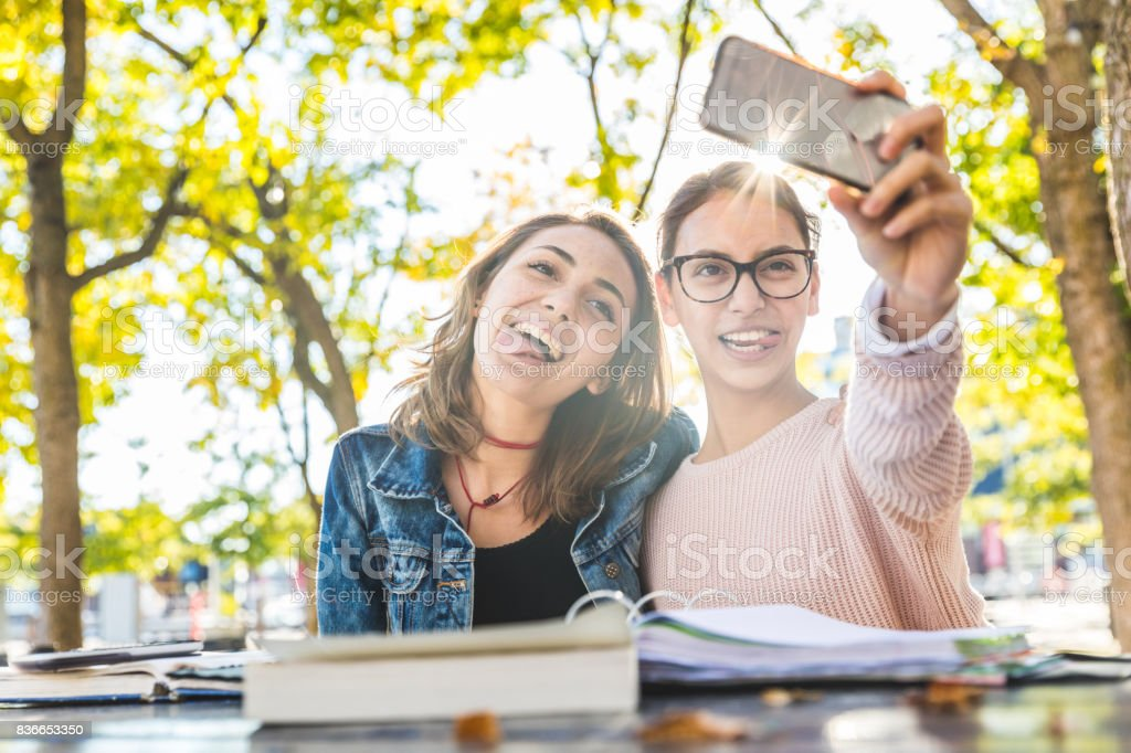 Girls studying and taking a funny selfie at park stock photo